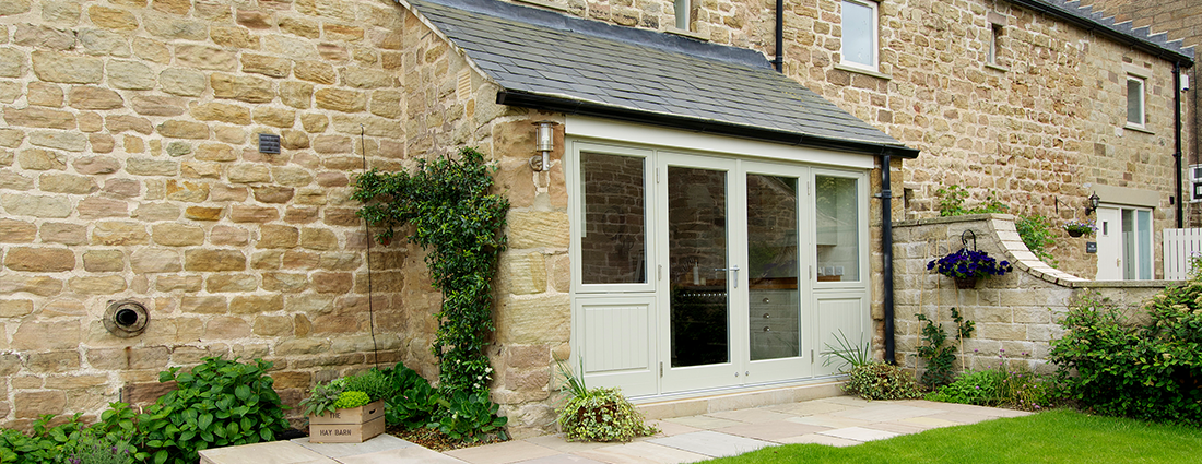 barn house with green wood patio doors and windows