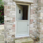 half open sage green wooden stable door