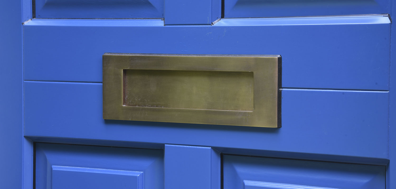 Blue wooden door with brass letterbox