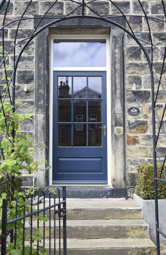 blue wooden front door with large windows and gold handle