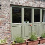 four sage green wooden windows and panels