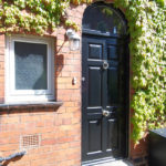 black wooden door with silver knob and knocker