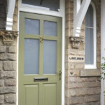 green wooden front door with gold handle and knocker