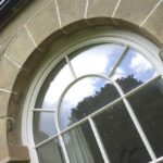 large arched wooden white window