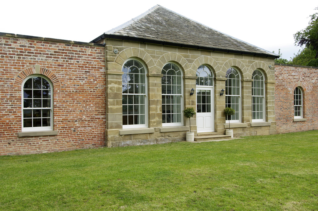 large arched white wooden windows with white wood door