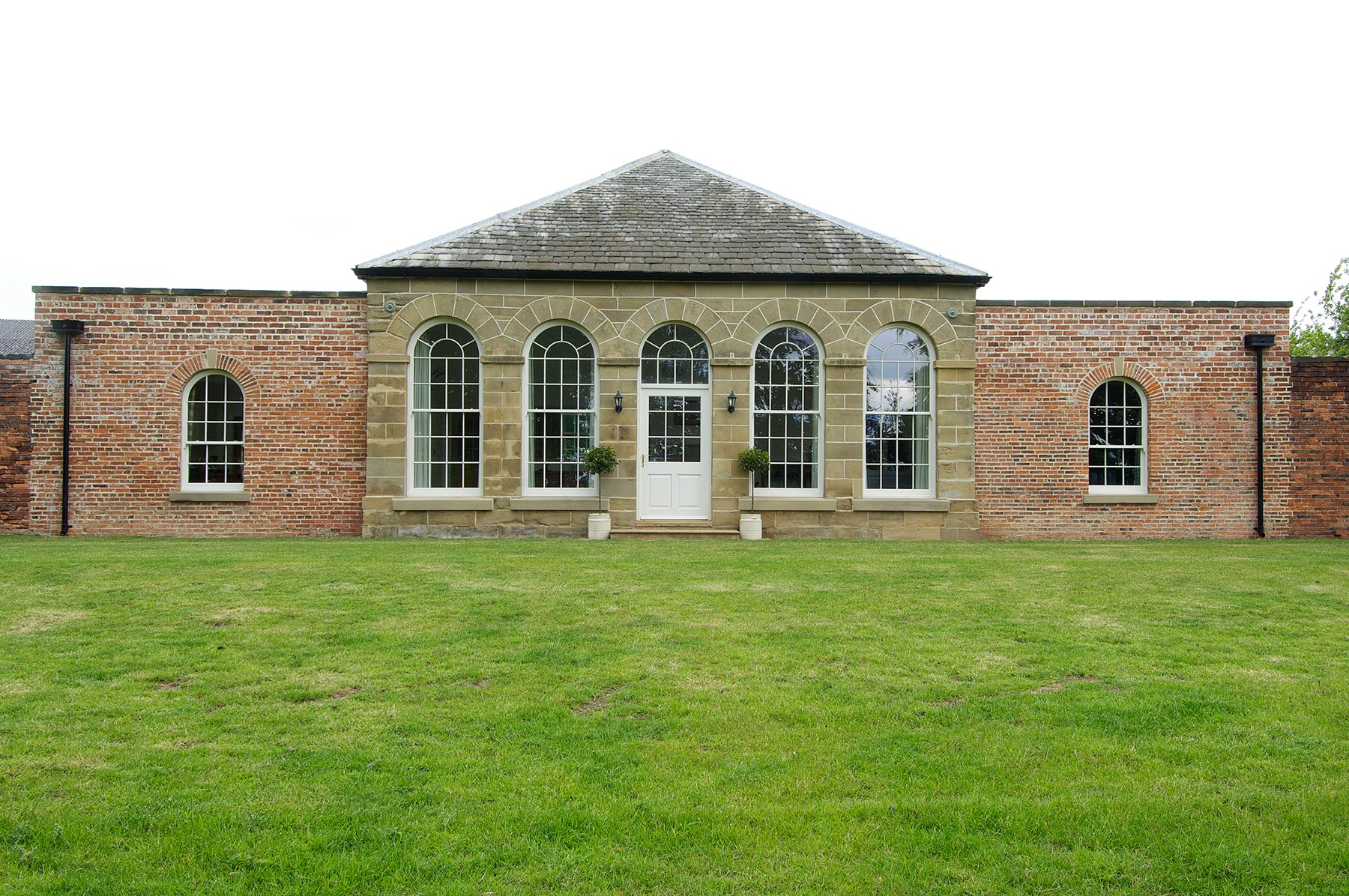 large white arched wooden windows with white wood front door