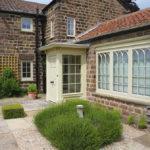 cream wooden windows with cream wooden front door