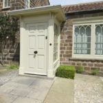 cream wooden front door and arched wooden windows