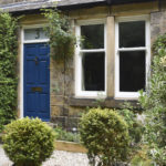 blue wooden front door with white wooden sash windows