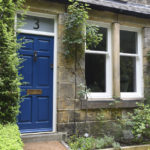 Blue wooden front door with gold letterbox and white wooden windows