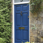 blue wooden front door with brass accents and frosted window