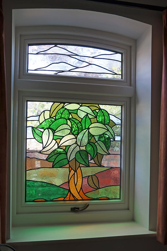 white wooden window with stained glass tree details