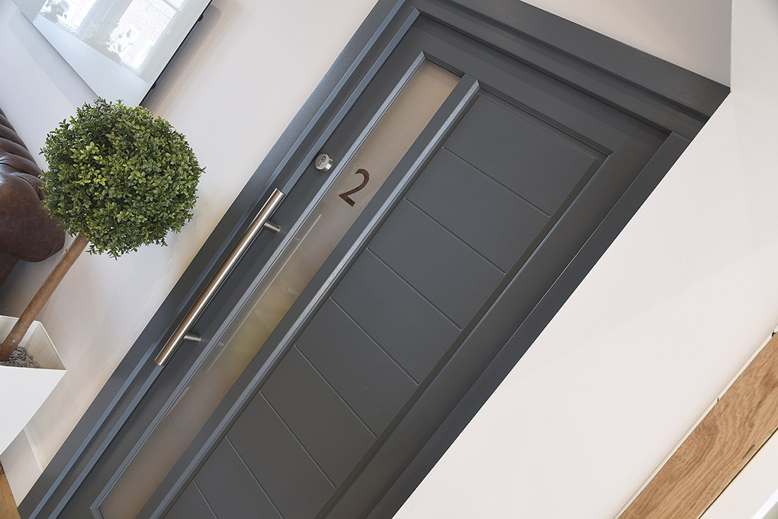 grey wooden front door with large silver handle