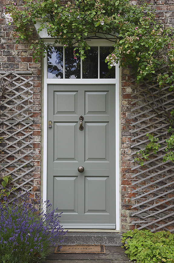 green wooden front door with bronze knob and knocker