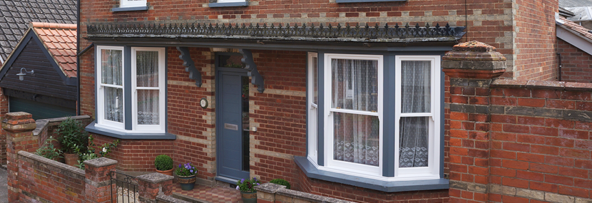 grey wooden front door with white wooden sash windows