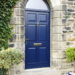 blue wooden front door with gold accents