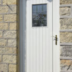 white wooden back door with stained windows
