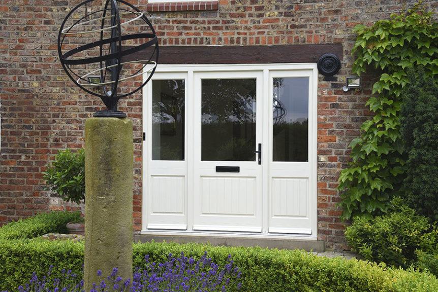 white wooden door with three windows and black door handle