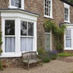 white wooden windows with sage green wooden front door