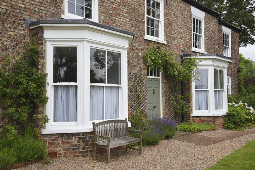 white wooden windows with sage green wooden front door