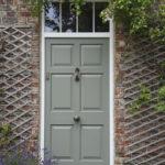 green wooden front door with bronze knob and knocker