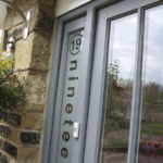 grey wooden front door with frosted window