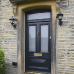 black wooden front door with gold accents