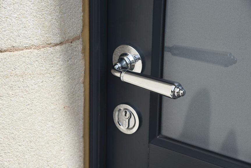 black wooden front door with silver door handle and lock