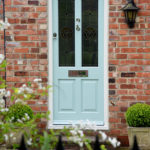 teal wooden front door with stained glass windows