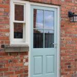 teal wooden front door and sash window