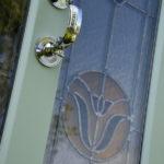 green wooden door with chrome plated door knocker