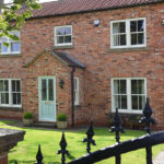house with white wooden sash windows and sage green wooden front door