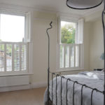 bedroom view of white wooden windows